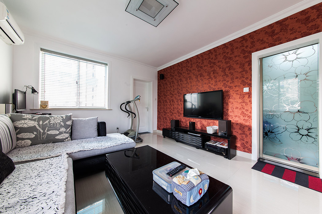 客厅采用淡色系的地砖,运用重色调的沙发、茶几来显现客厅的整体空间,电视背景墙的简单设计使得客厅的这个空间得到点缀,深色墙纸浅色地砖形成一体的视觉拉伸。