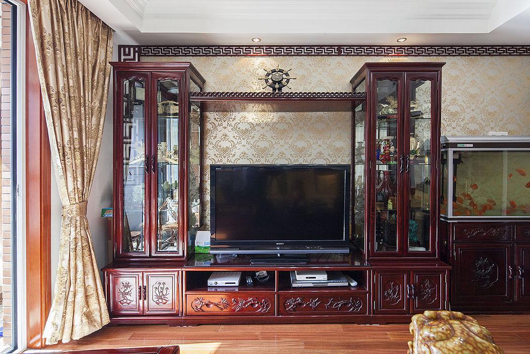 电视背景墙由传统的红木家具配上金色的墙纸,体现中式文化深沉、厚重的底蕴。