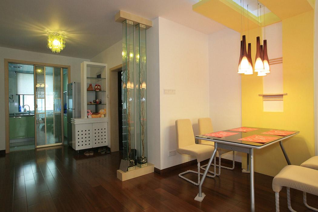 在淡黄幽深的灯光下,餐厅与厨房间大面积的空白正是现代简约风格的一种表现,它给人们留下更多的想象空间,入户门边的镂空鞋柜不仅给人更多的视觉空间,也是一种现代美。厨房与客厅间的透明玻璃隔断,