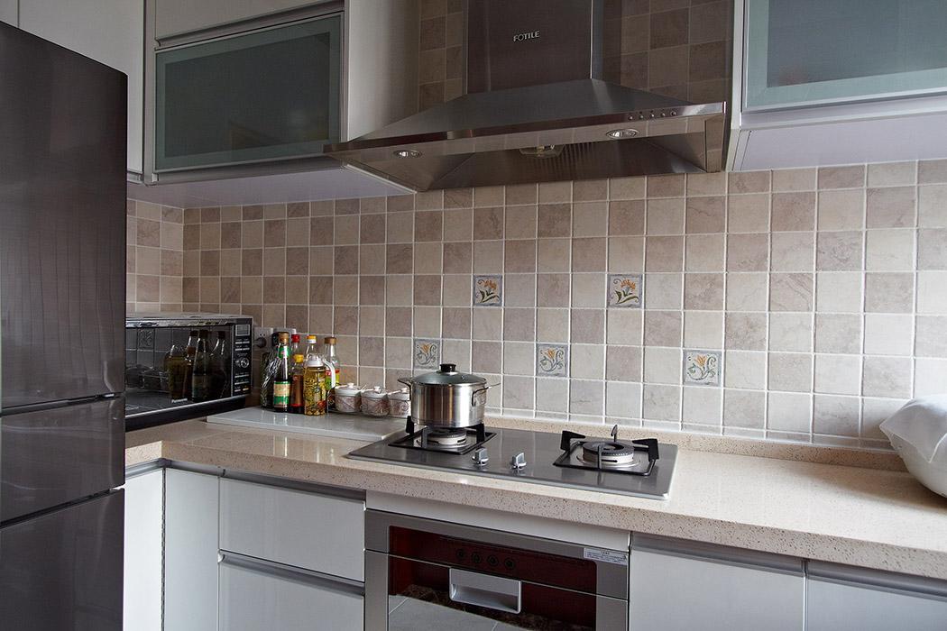 厨房运用错杂镶嵌的小花砖,但是整体橱柜运用整体统一的浅色色调,浅黄色的台面、现代简约的厨具表的得体大方。