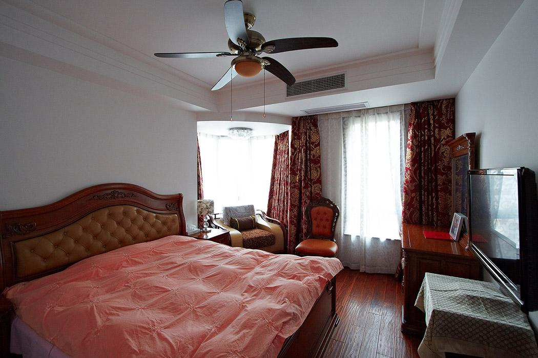 主卧奢华低调,现代韵味的吊扇,集休闲与休息与一体,红色带花的窗帘,配上红木色的家具,使得中式的传统文化表现的更加到位,简单的红木家具是主人的品味独特体现。