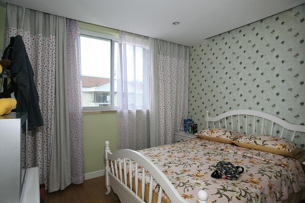 卧室中淡绿色的墙面、碎花图案的壁纸与床品、欧式田园风格的白色家具,营造出一个温柔梦幻的私密空间。简洁白色的天花,蕾丝的窗帘散发出甜美的气息。