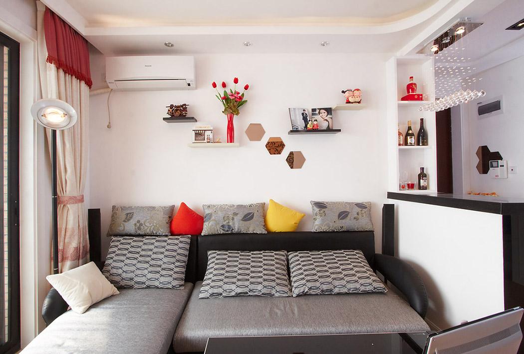 沙发上,错落有致的隔板摆放着旅游回来的纪念品和小照片,给客厅的空间增添了几分温馨的氛围。