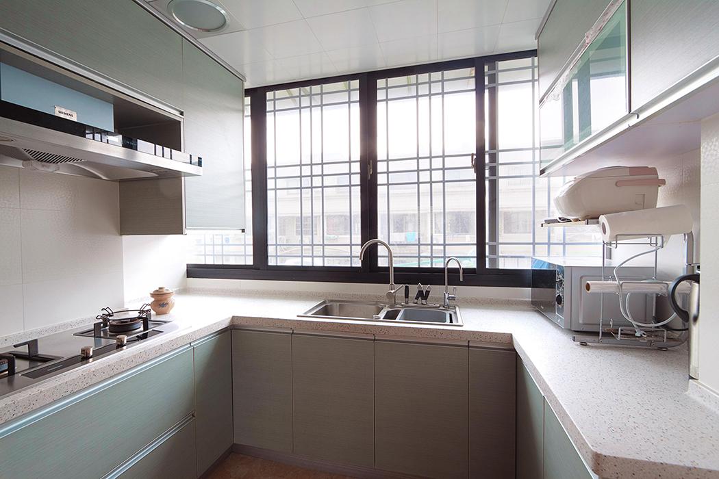 厨房间的搭配可算是别有用心,水槽处的柜面使用的是浅色的木色,呼应客厅处的木色,其余的柜体使用浅浅的绿色,使人心情愉快。