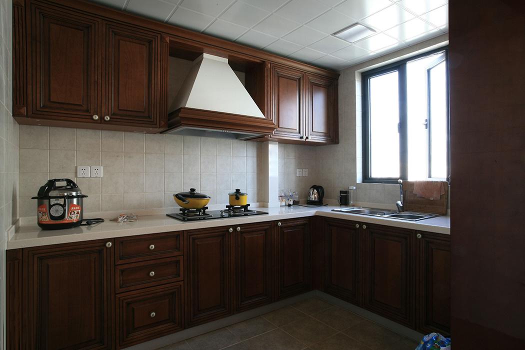 厨房间的整体橱柜都有着西式的风味,而且还带有西式田园风格。洁白的台面,吸油烟机的半露再有边框装饰,就更加突出了。