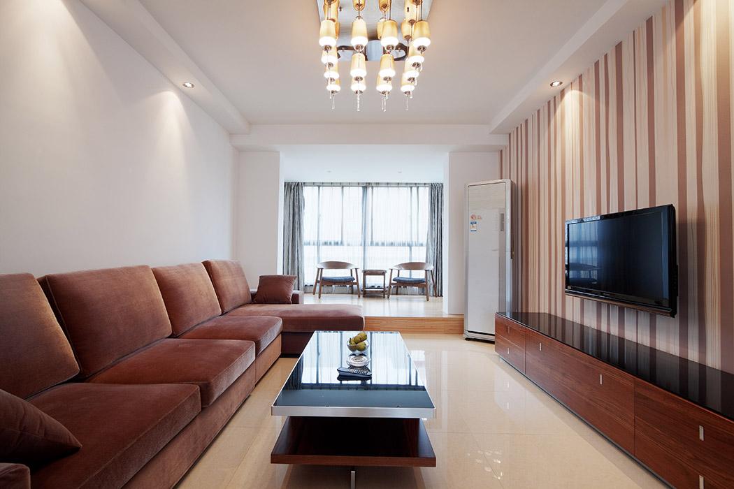 客厅中条纹图案的壁纸在白色的环境中塑造出有型的立面效果。 整个空间中只有少许的装饰品,干净,整洁的,落落大方。色泽统一的红色家具庄重严谨的感觉中又有一份活跃,加上多盏筒灯的点缀,空间很温暖,为方便舒适的生活做出了完美的诠释。