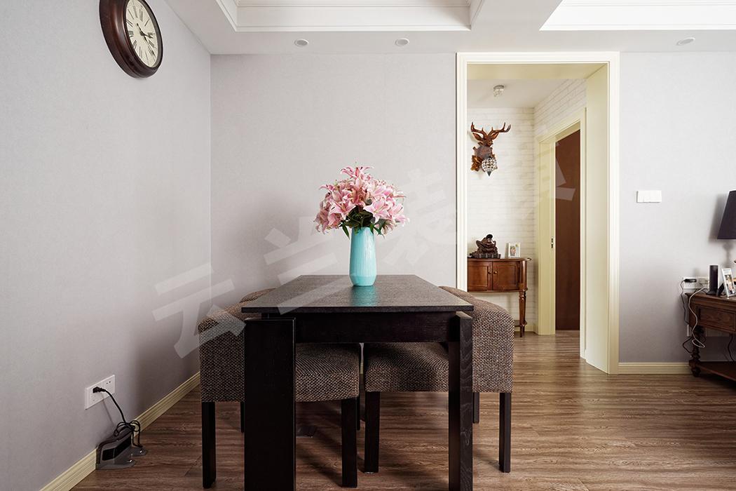 简易的蓝灰色壁纸,简易的木质餐桌和布艺餐椅,一只花瓶作为小小的点缀,一切恰到好处。