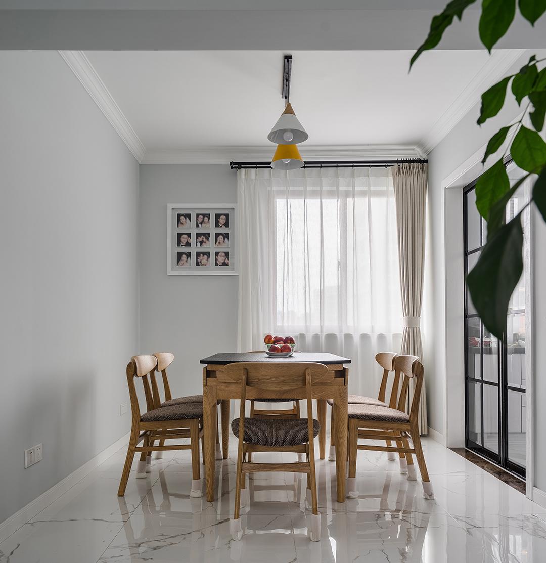 在餐厅的设计上,我们延续了客厅的灰调,明黄色餐厅灯给整个空间多了一丝明快,原木色的餐椅以及深色坐垫现代感分明,浅色窗帘元素中削减了空间的硬度。黑色格子玻璃门与餐厅风格保持协调统一。