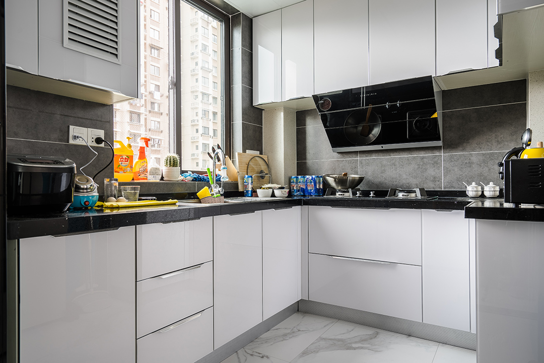厨房空间不算小,色调以黑白灰为主,橱柜门板特意选用金刚板,提亮空间亮度,而且方便打理,很清爽舒适。