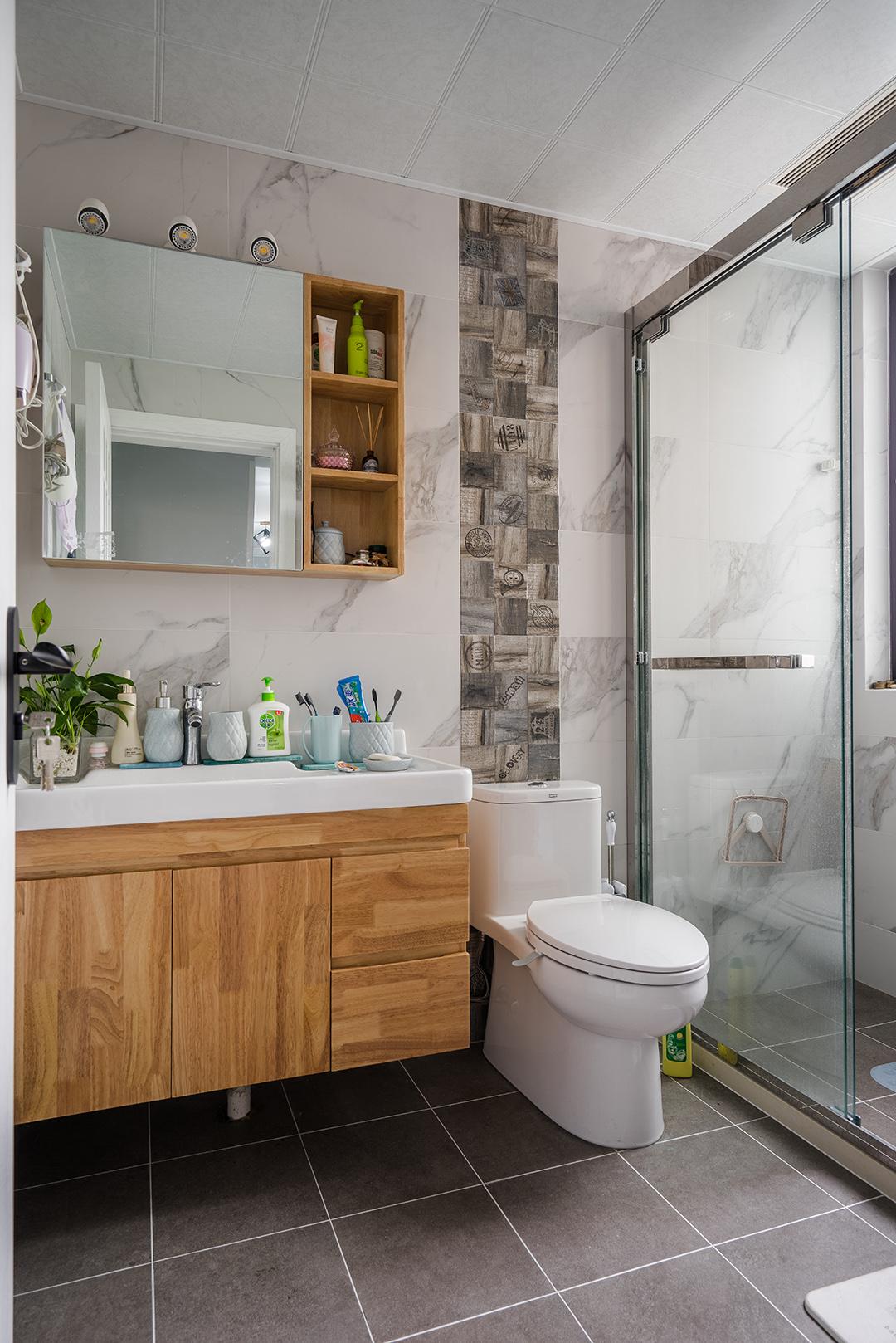 卫生间灰色地砖配上白色墙砖层次分明,马桶背后的腰带设计点亮了整个空间。