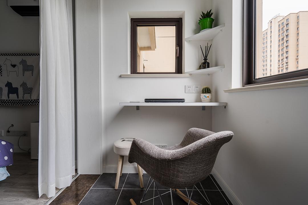 阳台是主人休闲工作的一个小天地,宜工作宜休闲。白色层板书作书架化繁为简,实用用且不占用空间。地砖选用灰黑色仿古砖配上白色美缝,再加上布艺小摇椅,好看。
